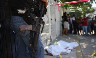 ACAPULCO, MEXICO - MARCH 02:  A policeman watches a sheet-covered body at a suspected drug-related double execution on March 2, 2012 in Acapulco, Mexico. Drug violence has surged in the coastal resort in the last year, making Acapulco the second most deadly city in Mexico after Juarez. One of Mexico's top tourist destinations, Acapulco has suffered a drop in business, especially from foreign tourists, due to the violence. Toursim accounts for about 70 percent of the economy of Acapulco's state of Guerrero and 9 percent of Mexico's economy.  (Photo by John Moore/Getty Images)