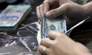 An employee counts U.S. dollar bank-notes near Vietnamese dong bank-notes at a bank in Hanoi, Vietnam